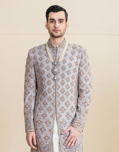 Oyester color sherwani  in matka silk fabric ,with all over intricate resham and zardosi work .Paired with long length kurta and churidar.