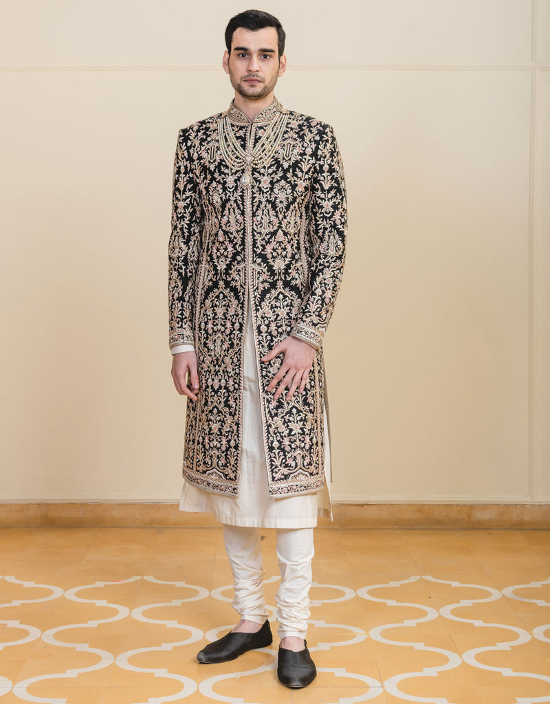 Black color sherwani in matka silk fabric with all over zardosi ,thread and zari work.Paired with long length kurta and churidar.