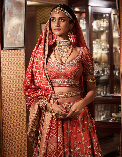 Bridal Lehenga In Raw Silk Highlighted With Zardozi Embroidery, Paired With A Brocade Blouse And Bandhini Dupatta. Styled With An Embroidered Belt.