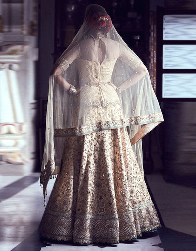 Bridal Lehenga In Silk Highlighted With Gota Flowers And Mirror Embroidery, Paired With A  Peplum Blouse And A Tulle Dupatta.