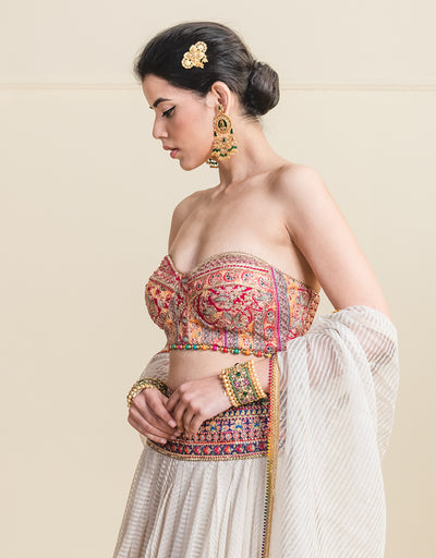 Draped Lehenga With An Embroidered Hip Yoke. Paired With An Embroidered Paneled Corset, Highlighted With Multi Coloured Beaded Tassels.