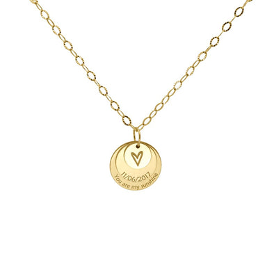 a gold necklace with 3 discs and a heart in the middle