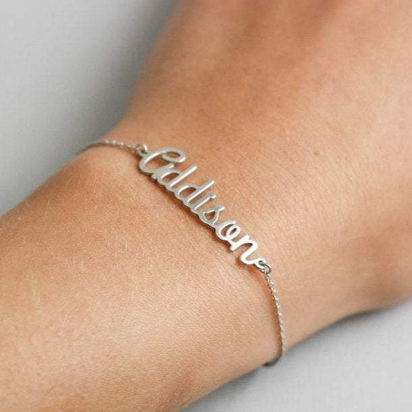 A silver necklace with the name Addison worn on someone's wrist