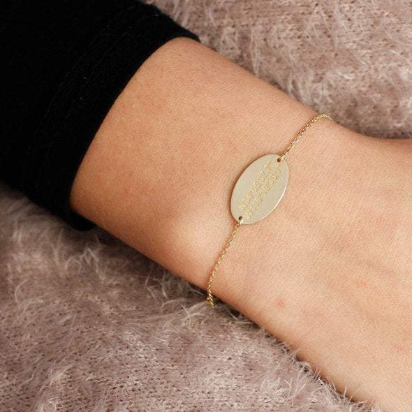 A gold coordinates oval bracelet on a wrist