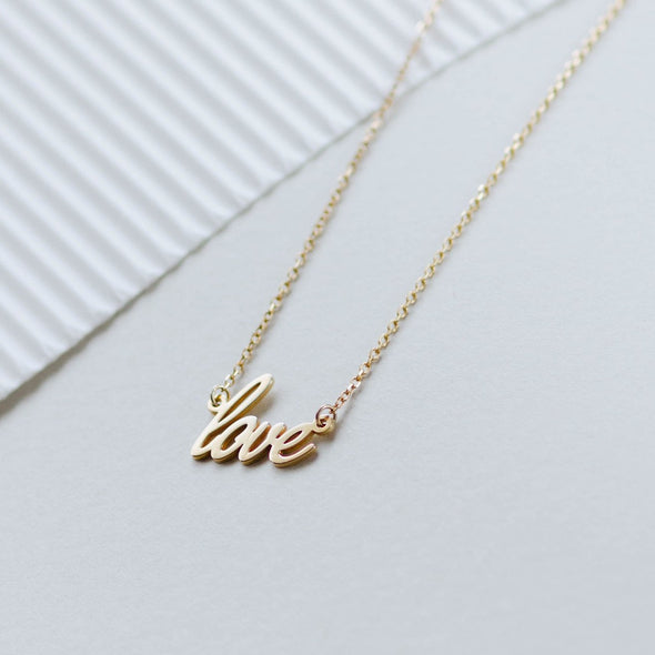 "a gold ""love"" chain necklace"