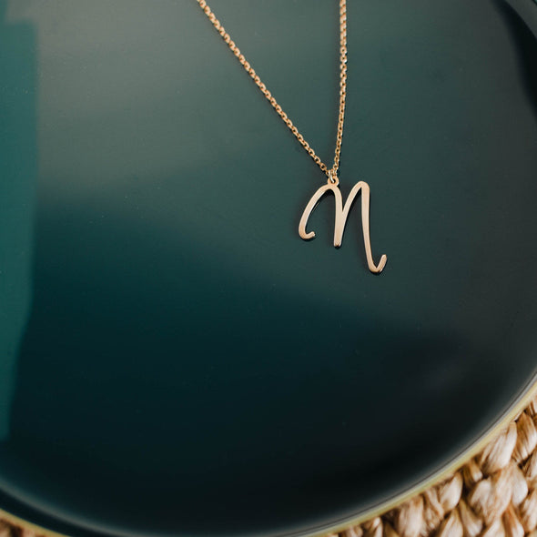a gold initial necklace with the letter ''M'' on it