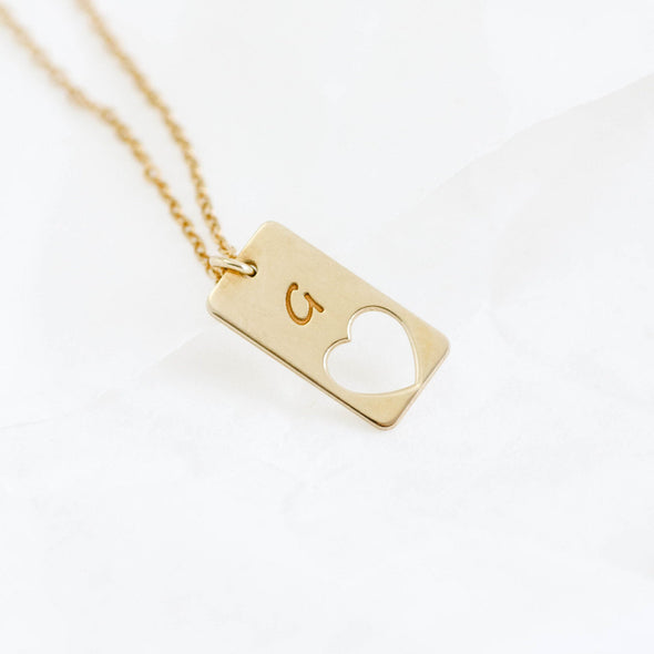 a gold necklace with a hollow heart inside it