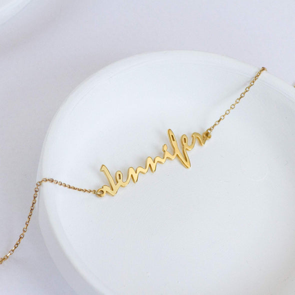 A golden name bracelet with the name Jennifer in calligraphy