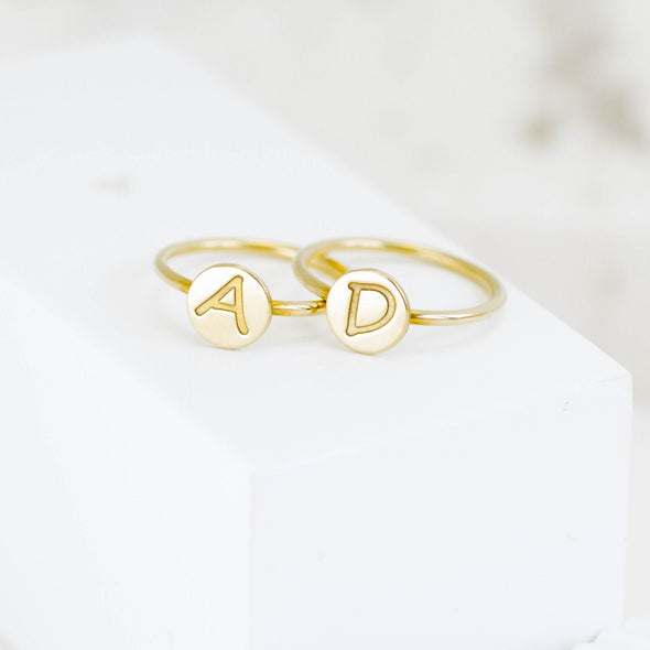 two gold rings with initials on them
