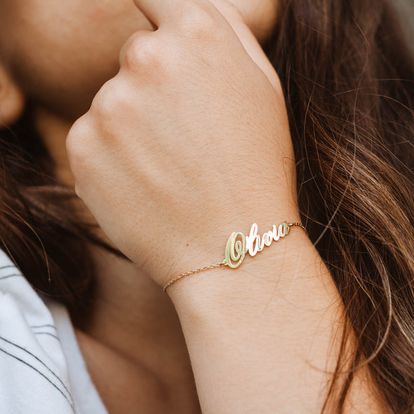 gold name bracelet on a hand