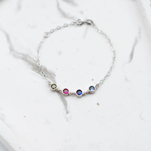 a silver bracelet with four birthstones