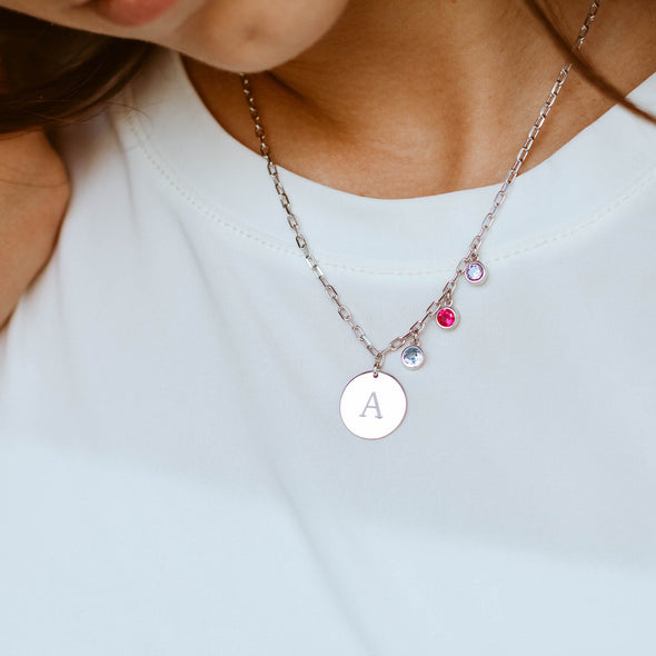 a sterling silver initial disc necklace with three birthstones