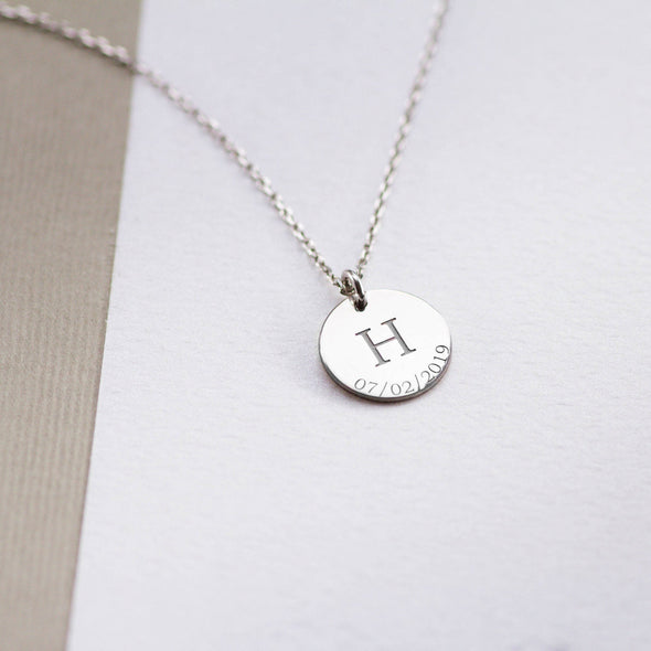 a silver disc necklace with initial and a engraved on it