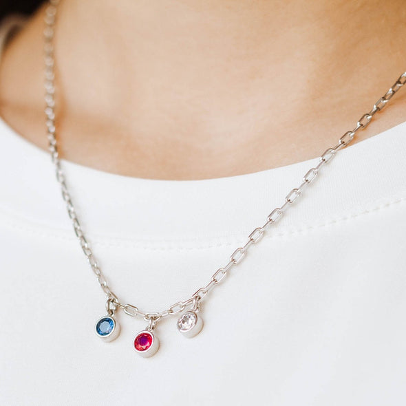 a silver necklace with three birthstones
