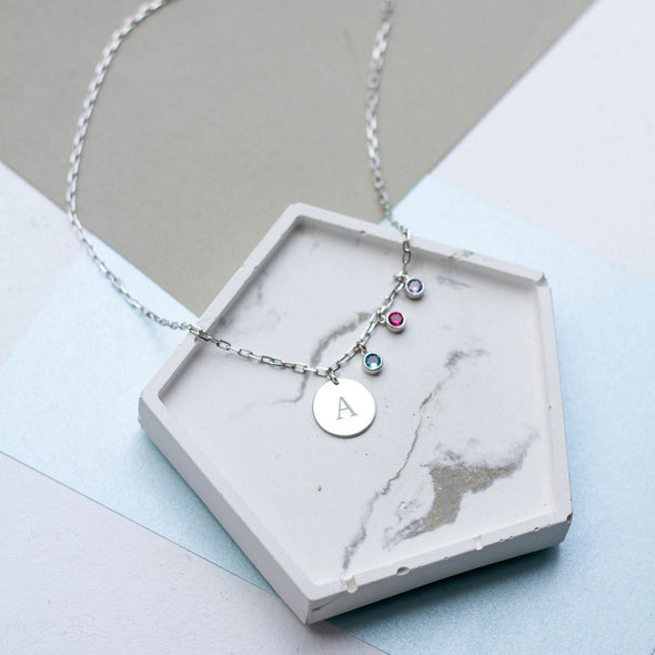 a silver initial disc necklace with three birthstones