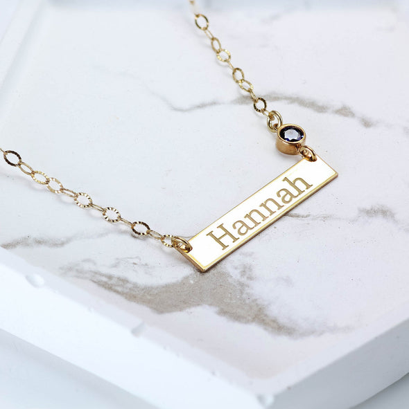 A gold name bar necklace with a birthstone on it
