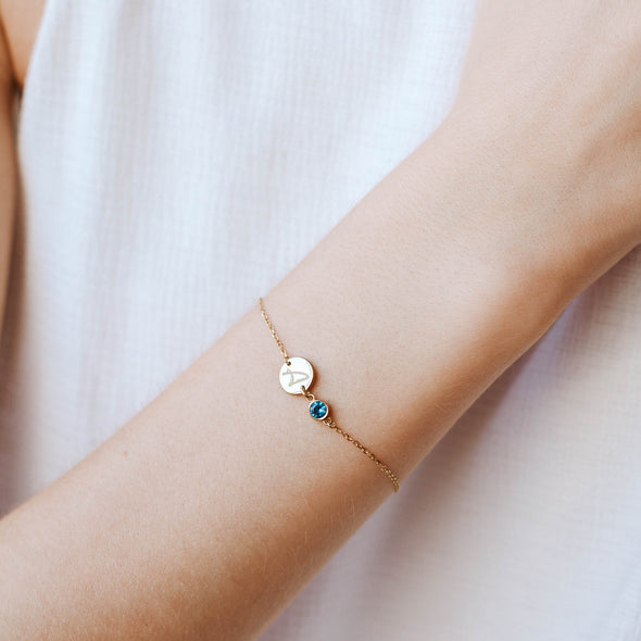 a disc initial birthstone bracelet in gold colour