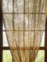 burlap-curtains-hanging-in-window-with-light-coming-through-225x300