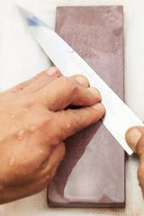 honing-chef-knifeclose-up-of-hand-working-japanese-chef-knife-200x300