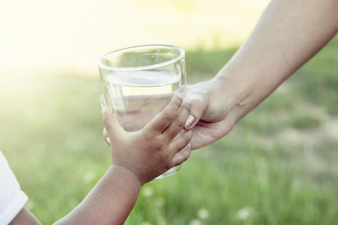 woman-hand-giving-glass-of-fresh-water-to-child-1024x682