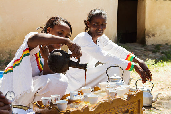 Two Ethiopian Girls brewing coffee using a traditional Jebena.