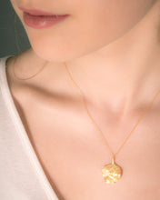 Model wearing textured petal flower pendant necklace