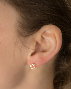 Model wearing geometric style cube earring in silver