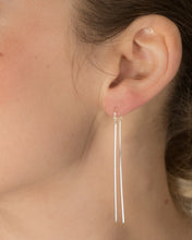 Model wearing long fine bar thread earrings silver