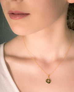 Small gold compass necklace on model
