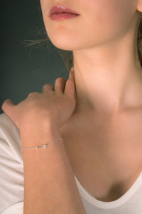 Model wearing small arrow charm bracelet