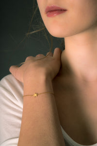 Model wearing star bracelet in gold