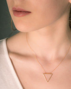 Model wearing modern geometric triangle pendant in gold