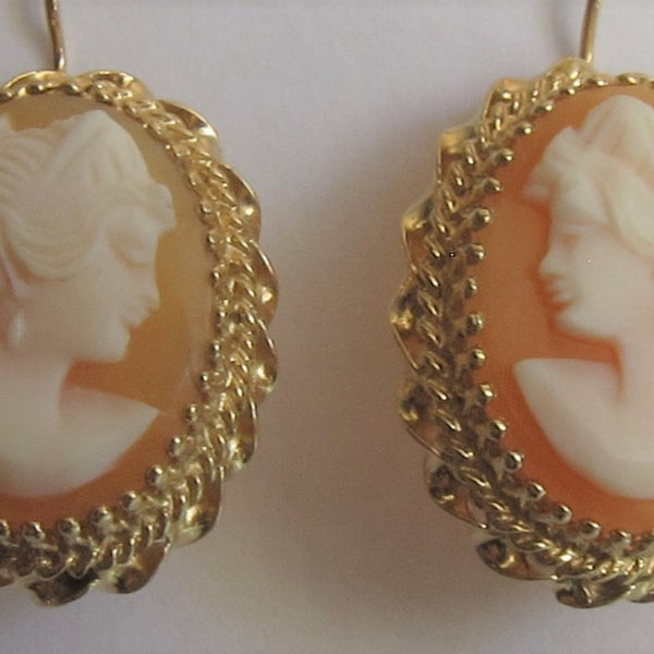 Close up of natural carved shell Cameo earring in 14 karat yellow gold.