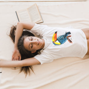 woman laying in bed wearing toucan hand painted white t-shirt design