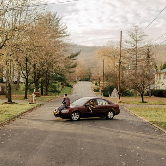 Driver by Adult Mom on Lauren Records (the album cover is a colour photograph of a suburban street with a car stopped across the width of it; one person leans out of the driver's window, while another sits casually on the hood of the car; there is no one else in the photograph)