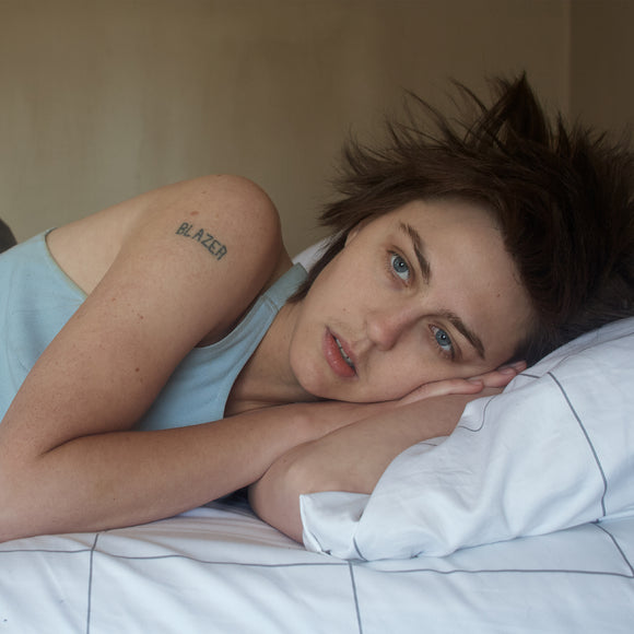 I Saw First Light by Anna McClellan on Father/Daughter Records (the album cover is a full-sleeve colour medium close-up photograph of Anna McClellan lying on a bed; McClellan wears a vest and has bed-head hair; on their bare right shoulder is a tattoo of the word 'BLAZER'