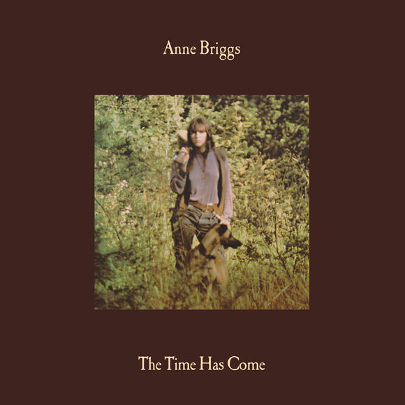 The Time Has Come by Anne Briggs on Earth Recordings (the album cover has a square colour picture of Anne Briggs standing in a woods holding a bouzouki over her shoulder, staring at the camera with a dog at her feet, obscured by long-grass; the photograph is surrounded by a wide brown border; the artist name appears above, and the album title below)