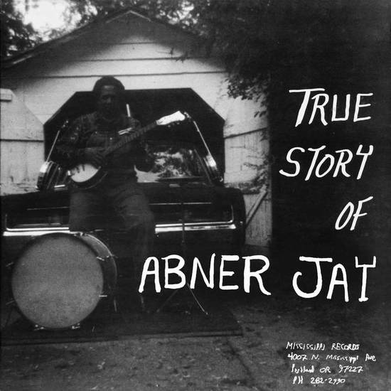 True Story Of Abner Jay by Abner Jay on Mississippi Records (the album cover is a borderless black and white, poorly-lit photograph of Abner Jay sat on a car bonnet holding a banjo with a bass drum and hi-hat at his feet; the album title is hand-written in white atop the right-hand side of the image)