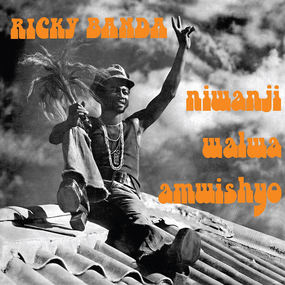 Niwanji Walwa Amwishyo by Ricky Banda on Now-Again Reacords (the album sleeve is a black and white photograph of Ricky Banda sat on a rooftop against a dramatically cloudy sky; Banda wears flared jeans, platform shoes, a vest, necklaces and hat, and their left hand is raised in a peace sign; the artist's name is printed in an orange uppercase seventies font; the album title is printed in lowercase in the same orange font))