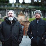 Band photograph by Kat Gollack of  Aidan Moffat and Malcolm Middleton of Arab Strap stood outdoors at Glasgow cemetery. It must be cold because they are wearing their coats buttoned up and have beards