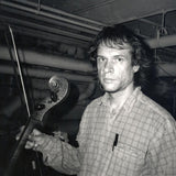 Black and white photograph of Arthur Russell. In the photograph, Russell is looking at the camera whilst holding a bow and the neck of a cello in their right hand. The photo is taken in a room with a low ceiling and pipes along the walls.
