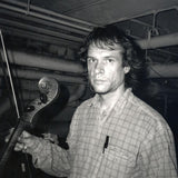 Black and white photograph of Arthur Russell. In The photograph, Russell is looking at the camera whilst holdinga bow and  the neck of a cello in their right hand. The photo is taken in a room with a low ceiling and pipes along the walls. Russell's hair is slightly wild, and they have a pen tucked into the pocket of their checked shirt.