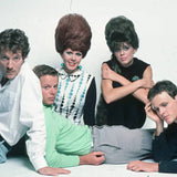 Photograph of The B-52's in 1980. The band (Fred Schneider, Ricky Wilson, Kate Pierson, Cindy Wilson, and Keith Strickland) are sat on a white floor, against a white background.
