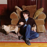 Lou Barlow sits on a rug on the floor in front of a soft brown chair, accompanied by two brown cats.