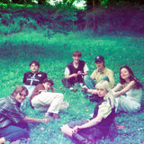 Band photograph of Black Country, New Road. The Band are sat in a meadow, roughly in a circle, and are all looking at the camera