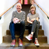 Stewart Anderson and Christina Riley of Boyracer; photograph is a candid shot of the two band-members sat on carpeted stairway laughing; both are dressed in black and white striped tops, jeans, and red shoes; they match, but not really)