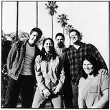 Black and white band photograph The Breeders in 2002. The photograph shows the five members of the band stood together facing the camera in a jovial way. They are stood in front of a row of palm trees. From left to right the photograph shows Mando Lopez, Kim Deal, Richard Presley, Jose Medeles and Kelley Deal. Photograph by Pieter Van Hattem