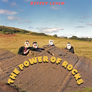 The Power Of Rocks by Buffet Lunch on Upset The Rhythm Records (the album cover is a photograph of the band, wearing naive masks, stood behind a large rocky outcrop in a field).