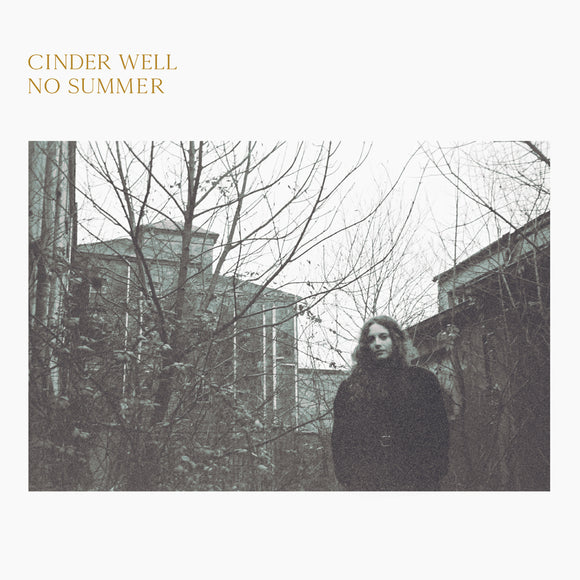 No Summer by Cinder Well on Free Dirt Records (the album cover features a black and white rectangular photograph of Amelia Baker stood in front of leafless trees and stone buildings beneath a white sky; the photgraph is on a plain white background, and the artist name and album title are printed in a n uppercase light gold serif font at the top-left of the sleeve)