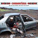 We Are An Island, But We're Not Alone by Comorian on Glitterbeat Records (the album cover features a photograph of a musician sat in the back door of a wrecked car, looking off-camera and holding a homemade acoustic guiar-like instrument, surrounded by microphones; the car appears to be near a cliff top, and beyond to horizon is the sea).